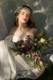 一套婚礼礼服的美丽的女孩在草 库存图片