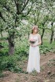 一套婚礼礼服的美丽的新娘与花束和玫瑰在一个绿色庭院里缠绕摆在 库存图片