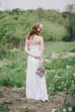 一套婚礼礼服的美丽的新娘与花束和玫瑰在一个绿色庭院里缠绕摆在 免版税库存图片
