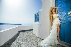 一套婚礼礼服的美丽的新娘在圣托里尼在希腊。 库存照片