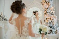 一套婚礼礼服的美丽的新娘在圣诞节的一个镜子 Gir 免版税库存照片