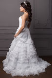 一套婚礼礼服的美丽的柔和的女孩新郎与发型和构成,用花花圈装饰的头发  免版税库存图片