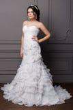 一套婚礼礼服的美丽的甜柔和的女孩新郎与一个花圈和花在她的头发在演播室 免版税库存图片