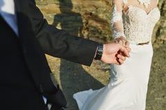 一套婚礼礼服的Photoshoot恋人在海附近的山 免版税库存照片