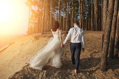 一套婚礼礼服的Photoshoot恋人在海附近的海滩 免版税库存图片