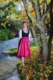 一套少女装的美丽的妇女在秋天树下 库存图片