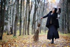 一套巫婆衣服的一名妇女在森林里 免版税图库摄影