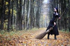 一套巫婆衣服的一名妇女在森林里 库存图片