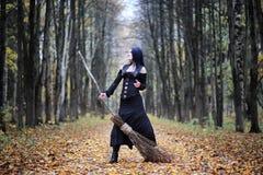 一套巫婆衣服的一名妇女在森林里 库存照片