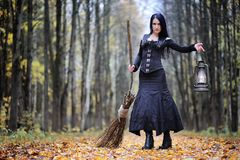 一套巫婆衣服的一名妇女在森林里 免版税库存照片
