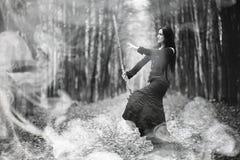 一套巫婆衣服的妇女在一个密集的森林里 免版税图库摄影