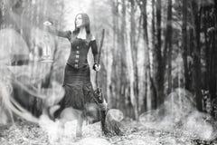 一套巫婆衣服的妇女在一个密集的森林里 库存照片