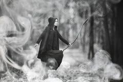 一套巫婆衣服的妇女在一个密集的森林里 库存图片