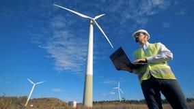 一套有操作他的膝上型计算机的一位男性工程师的风车在它旁边 干净,环境友好的能量概念 股票视频
