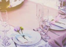 一套杯与利器的婚礼设置有紫罗兰色花的上升了 事件党或结婚宴会的表 库存图片