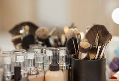 一套构成的刷子和定调子站立在一个镜子前面的桌上的人的基础在美容院 库存图片