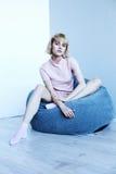 一套桃红色家庭衣服的一个女孩在一把软的椅子附近 时装杂志的美好的模型姿势 在镇静灰色蓝色口气的图片 免版税库存图片