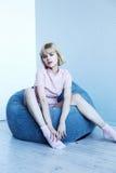 一套桃红色家庭衣服的一个女孩在一把软的椅子附近 时装杂志的美好的模型姿势 在镇静灰色蓝色口气的图片 免版税库存照片