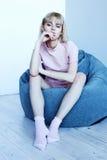一套桃红色家庭衣服的一个女孩在一把软的椅子附近 时装杂志的美好的模型姿势 在镇静灰色蓝色口气的图片 库存图片