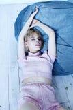 一套桃红色家庭衣服的一个女孩在一把软的椅子附近 时装杂志的美好的模型姿势 在镇静灰色蓝色口气的图片 免版税图库摄影