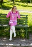 一套桃红色衣服的妇女在一条长凳在公园 库存图片