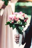 一套深蓝套装的未婚夫拿着婚礼花束由玫瑰做成 库存照片