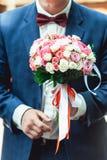 一套深蓝套装的未婚夫拿着婚礼花束由玫瑰做成 免版税库存图片