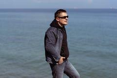 一套牛仔布衣服的一个人在海的背景在一春天好日子 图库摄影