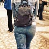 一套牛仔布衣服的女孩与在他的肩膀的一个袋子 库存照片