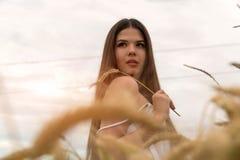 一套白色夏天衣服的一个女孩在一块麦田站立 女孩在她的手上握麦子耳朵 免版税库存图片