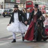 一套白色婚礼礼服的一个人和有一名妇女的一顶高顶丝质礼帽哥特式红色天鹅绒的在伦敦桥穿戴步行沿着向下街道 库存图片