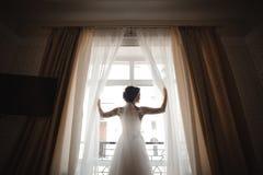 一套白色婚礼礼服的美丽的新娘打开帷幕 免版税库存照片