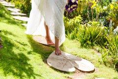一套白色婚礼礼服的美丽的年轻新娘与在h的花束 图库摄影