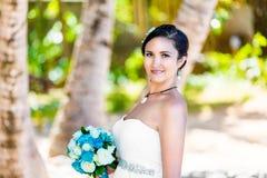 一套白色婚礼礼服的美丽的年轻新娘与在h的花束 免版税库存照片