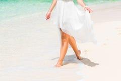 一套白色婚礼礼服的美丽的年轻新娘走在trop的 库存图片