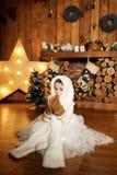 一套白色温暖的熊衣服和手套的一女孩在壁炉附近坐 在树上小屋里 节假日概念 库存图片