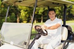 一套白色衣服的一个人驾驶一白色高尔夫球汽车和微笑 库存照片
