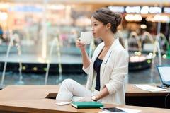 一套白色衣服的年轻,美丽的女孩,坐在咖啡馆在Th 免版税库存照片
