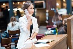 一套白色衣服的年轻,美丽的女孩,坐在咖啡馆在Th 免版税库存图片