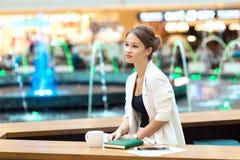 一套白色衣服的年轻,美丽的女孩,坐在咖啡馆在Th 库存照片