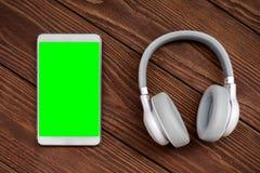 一套的一张顶视图无线耳机和空白的片剂模板说谎在一张土气木桌上的,书桌 库存照片