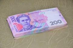 一套的特写镜头照片与200 hryvnia的面值的乌克兰金钱,说谎棕色皮革表面上 背景 免版税库存照片