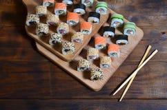 一套的详细的射击日本寿司卷和他们的用途筷子的一个设备,位于一条木切口蟒蛇 库存图片