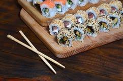 一套的详细的射击日本寿司卷和他们的用途筷子的一个设备,位于一条木切口蟒蛇 免版税库存图片