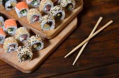 一套的详细的射击日本寿司卷和他们的用途筷子的一个设备,位于一条木切口蟒蛇 库存照片