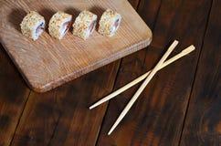 一套的详细的射击日本寿司卷和他们的用途筷子的一个设备,位于一条木切口蟒蛇 免版税图库摄影