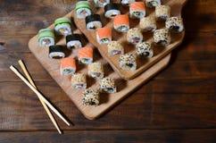 一套的详细的射击日本寿司卷和他们的用途筷子的一个设备,位于一条木切口蟒蛇 免版税库存照片