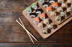 一套的详细的射击日本寿司卷和他们的用途筷子的一个设备,位于一条木切口蟒蛇 图库摄影