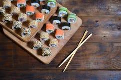 一套的详细的射击日本寿司卷和他们的用途筷子的一个设备,位于木切开的b 免版税库存图片