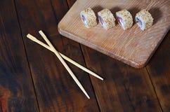 一套的详细的射击日本寿司卷和他们的用途筷子的一个设备,位于木切开的b 免版税库存照片